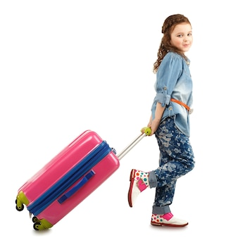 Full-length portrait of a pretty little girl with big pink suitcase on wheels isolated on white