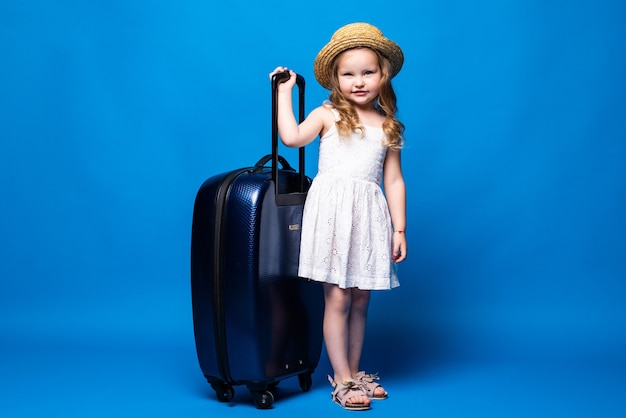 Ritratto integrale della ragazza graziosa del bambino con il bagaglio isolato sulla parete blu. passeggero che viaggia all'estero durante il fine settimana. concetto di viaggio di volo aereo.
