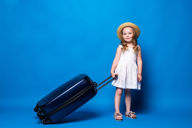 Full length portrait of pretty little kid girl with baggage isolated on blue wall. passenger traveling abroad on weekends getaway. air flight journey concept.
