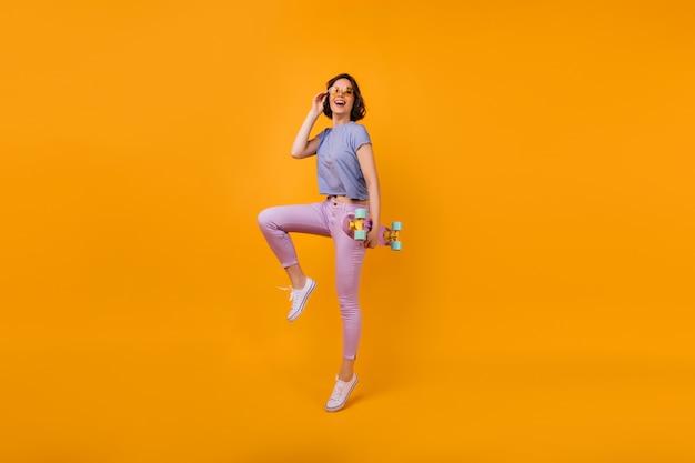 Ritratto a figura intera di una donna dai capelli corti piuttosto con il longboard. tiro al coperto di una ragazza spettacolare in abito estivo e occhiali di colore giallo.