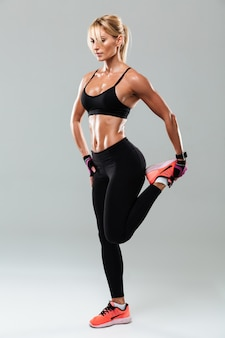 Full length portrait of a pretty sportswoman doing stretching exercises