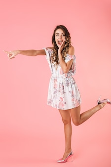 Full length of portrait of pretty woman with long hair wearing dress pointing finger aside, isolated on pink