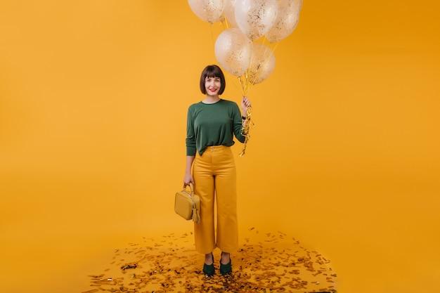 Ritratto integrale della donna graziosa con la borsa isolata. tiro al coperto della ragazza di compleanno alla moda che tiene mazzo di palloncini del partito.