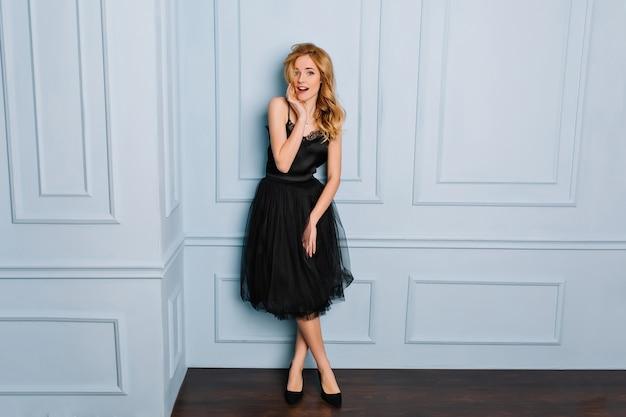 Ritratto integrale di bella giovane donna che indossa un abito nero elegante pizzo e scarpe in posa in camera con parete blu. è sorpresa, ha aperto la bocca. ha lunghi capelli biondi ondulati.