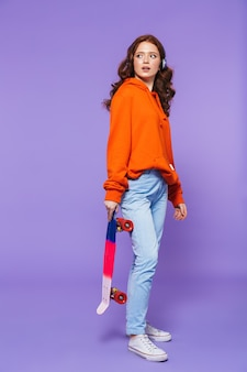 Full length portrait of a pretty young redheaded woman standing over violet, holding skateboard, listening to music with headphones