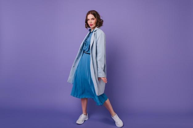Ritratto a figura intera di raffinata ragazza in scarpe da ginnastica e cappotto. estatica giovane donna in abito blu in posa con piacere sulla parete viola.