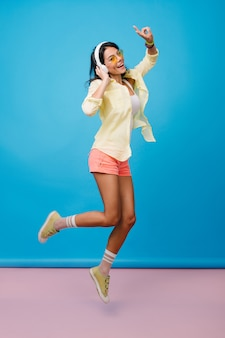 Full-length portrait of refined latin woman with tanned skin jumping and smiling. graceful slim girl in trendy socks wears big white headphones and listening music.