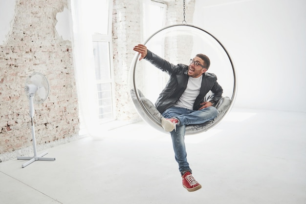 Full-length portrait of relaxed hipster man in casual sitting on hanging chair bullet and smiling on camera isolated over white
