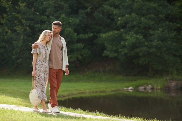 Full length portrait of romantic adult couple embracing while walking towards lake in beautiful nature scenery