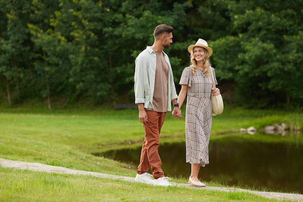 Full length portrait of romantic adult couple holding hands while walking by lake in rustic countryside scenery