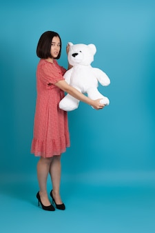 Full-length portrait of a sad angry woman pulling and tearing a white teddy bear