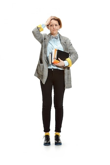 Full length portrait of a sad female student holding books isolated on white space
