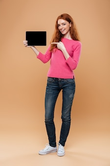 Full length portrait of a satisfied pretty redhead girl pointing finger at digital tablet