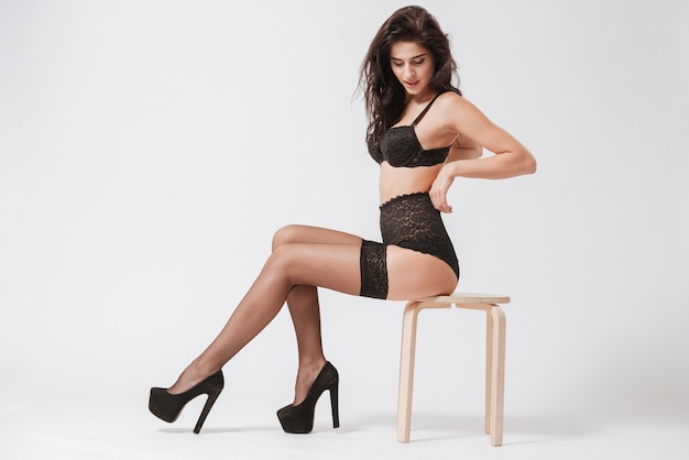 Full length portrait of a seductive sexy woman in lingerie with stockings sitting on chair and posing isolated