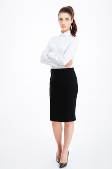 Full length portrait of a serious businesswoman standing with arms folded isolated on a white wall