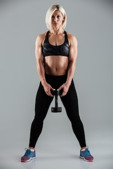 Full length portrait of a serious muscular adult sportswoman