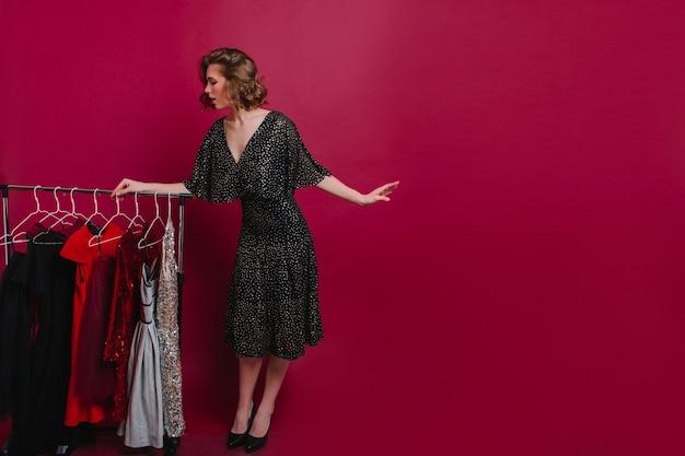 Ritratto a figura intera della ragazza formosa che sceglie abbigliamento elegante per la festa