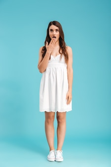 Full length portrait of a shocked young woman