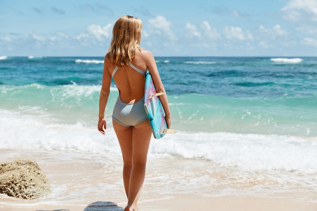 Full length portrait of slim female with light hair, wears blue swimsuit, stands against ocean beautiful view with waves, uses surf board for active sport activities, recreate during summer weather
