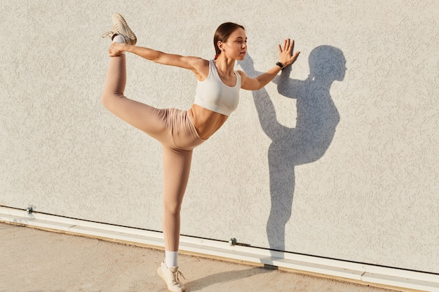 Full length portrait of slim female with perfect body, wearing white sporty top and beige leggins, standing on one leg and stretching body, leaning wall with palm.