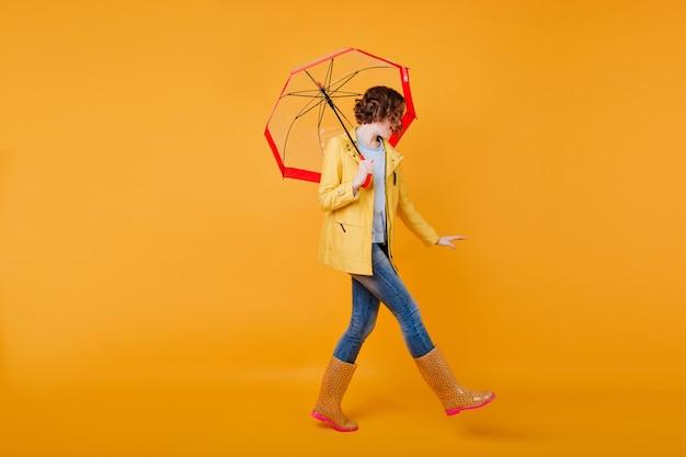 Ritratto integrale della ragazza sottile in scarpe di gomma divertenti che ballano con l'ombrello. signora castana riccia che si diverte durante il servizio fotografico in abito autunnale.