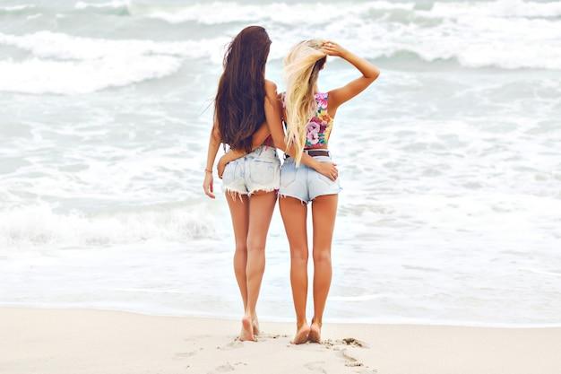 Ritratto integrale della ragazza sottile con capelli scuri lunghi che gode del paesaggio marino con il migliore amico.