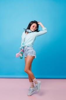 Ritratto a figura intera di donna ispanica sottile che esprime emozioni felici. sensuale ragazza latina con pelle abbronzata in abito da strada ballando con la mano in alto.