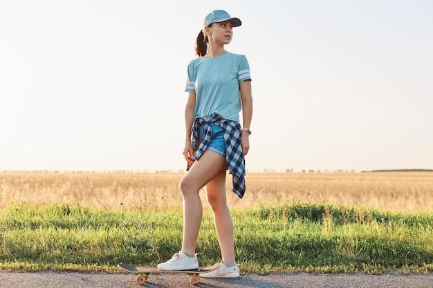 Ritratto a figura intera di donna sportiva esile che indossa maglietta e berretto con visiera, in piedi con la gamba sullo skateboard e distoglie lo sguardo, trascorrendo il tempo libero in modo attivo.