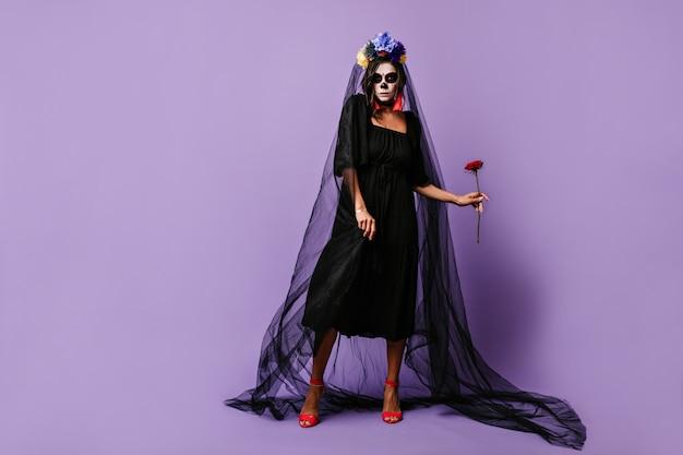 Ritratto a figura intera di donna sottile in abito da sposa nero. la ragazza castana con il trucco per halloween sembra minacciosamente