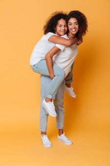 Full length portrait of smiling african girl carrying sister