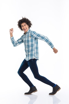 Full length portrait of a smiling afro american man running isolated on a white wall