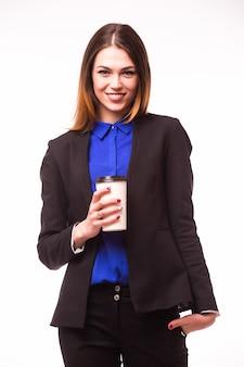 Ritratto integrale di una donna di affari asiatica sorridente che trasporta il computer portatile e la tazza di caffè per andare mentre levandosi in piedi isolato sopra la parete bianca