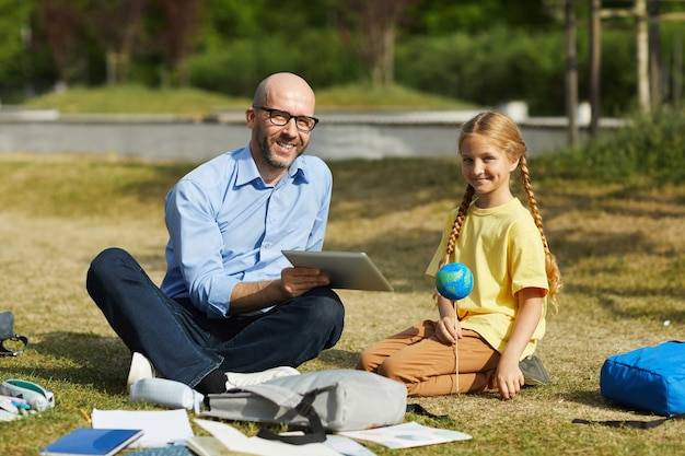 Full length portrait of smiling bald teacher looking at camera while enjoying outdoor astronomy lesson with cute blonde girl, copy space