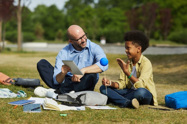 Full length portrait of smiling bald teacher talking to african-american boy holding model planet while enjoying outdoor astronomy lesson in sunlight, copy space