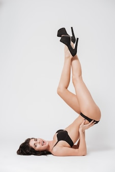 Full length portrait of a smiling brunette woman wearing sexy lingerie and laying with her legs raised isolated