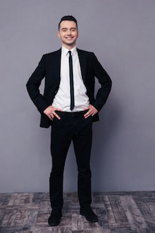 Full length portrait of a smiling businessman standing on gray wall