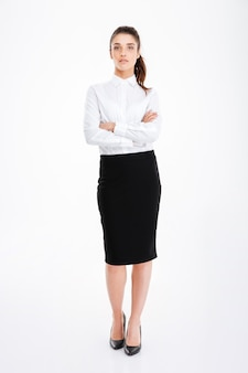 Full length portrait of a smiling businesswoman standing with arms folded isolated on a white wall