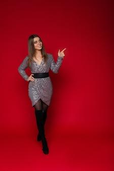 Ritratto integrale della ragazza allegra sorridente in vestito d'argento da cocktail e stivali alti neri che indicano lo spazio rosso della copia.