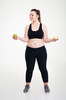 Full length portrait of a smiling fat woman choosing between donut and apple isolated on a white wall