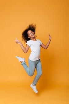 Full length portrait of a smiling little african girl jumping