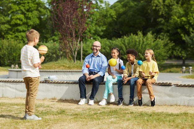 Full length portrait of smiling male teacher listening to boy giving presentation on astronomy while sitting with group of children and enjoying outdoor lesson in sunlight, copy space