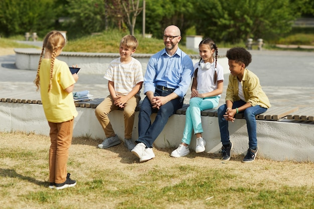 Full length portrait of smiling male teacher listening to little girl giving presentation while sitting with group of children and enjoying outdoor lesson in sunlight, copy space