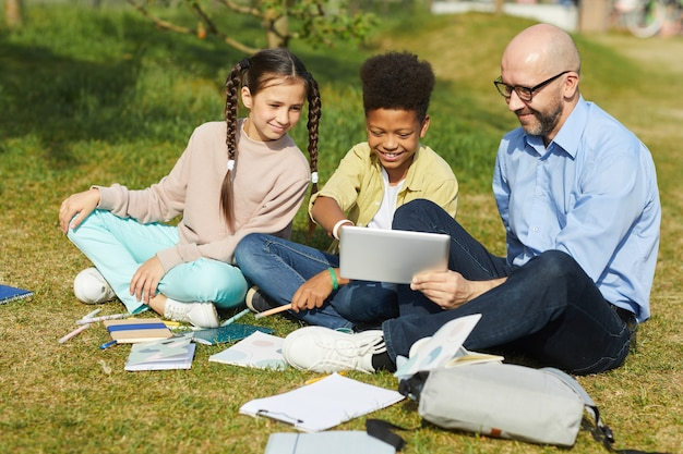 Full length portrait of smiling male teacher talking to children while sitting on green grass and enjoying outdoor class in sunlight