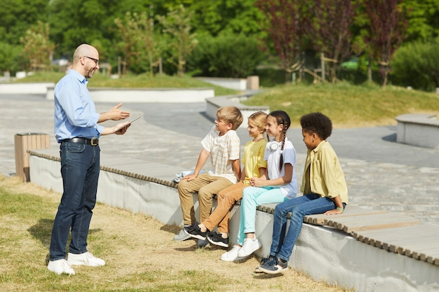 Full length portrait of smiling male teacher talking to group of children while enjoying outdoor lesson in sunlight, copy space