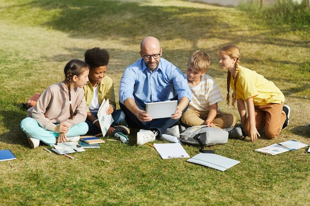 Full length portrait of smiling male teacher talking to group of children while sitting on green grass and enjoying outdoor class in sunlight, copy space