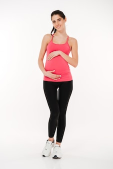 Full length portrait of smiling pregnant fitness woman