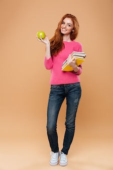 Full length portrait of a smiling pretty redhead girl holding books and apple