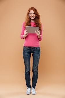 Full length portrait of a smiling pretty redhead girl holding tablet