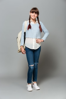 Full length portrait of a smiling pretty schoolgirl with backpack