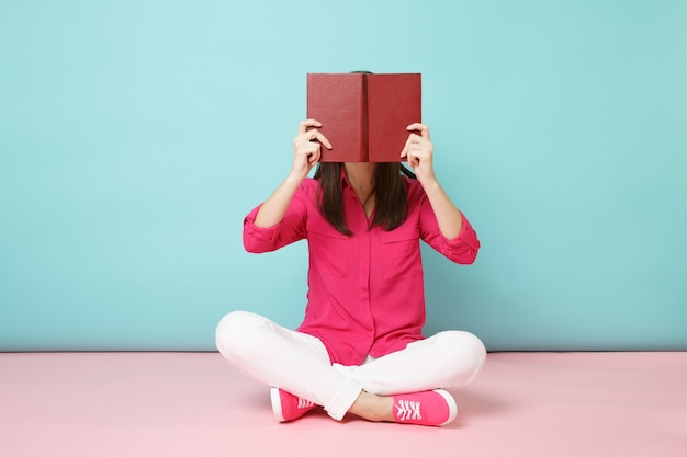Full length portrait of smiling woman in rose shirt blouse, white pants sit on floor read book